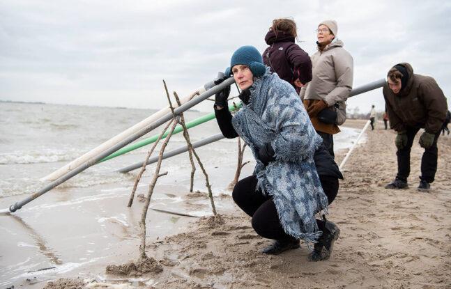 Dame houd oor tegen windpijp in zee