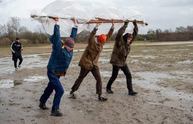 Jongeren dragen stokken met plastic zakken