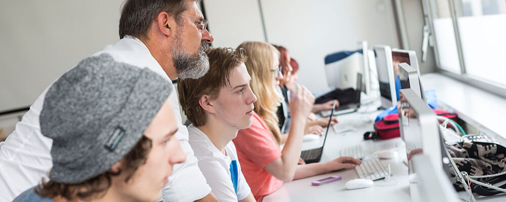 Leraar kijkt op mee op computer van student