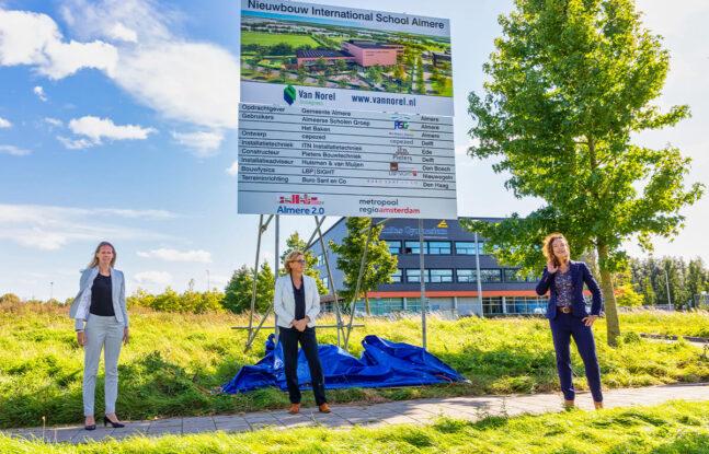 Vrouwen onthullen bouwbord Nieuwbouw International School Almere