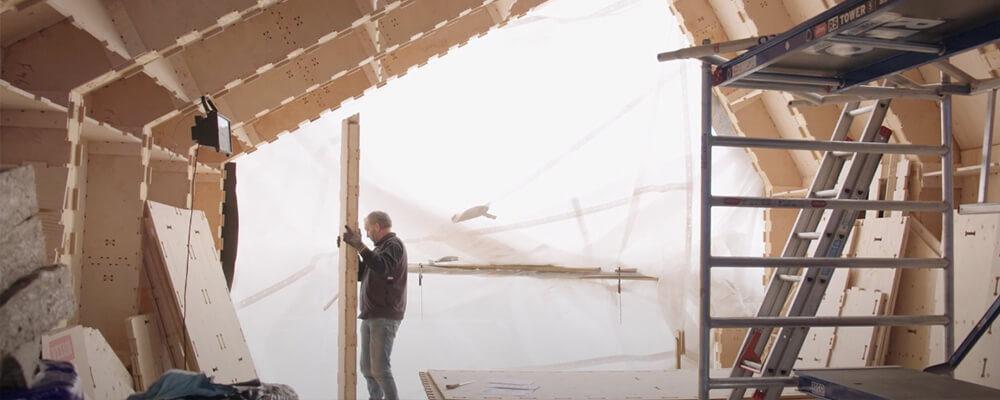Man draagt houten plaat binnen een WikiHouse