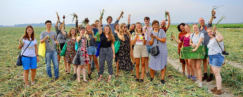 Studenten staan op veld met rode uien in hand
