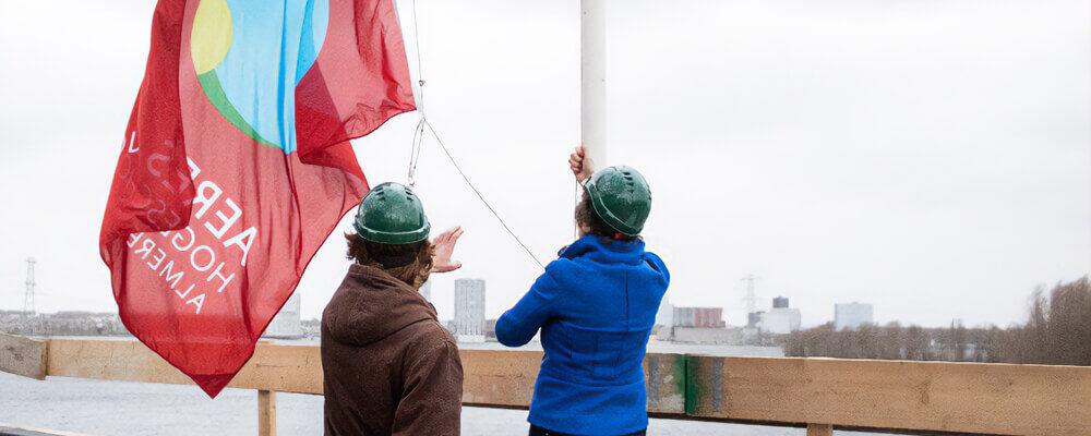 Twee personen heisen vlag Hogeschool Aeres