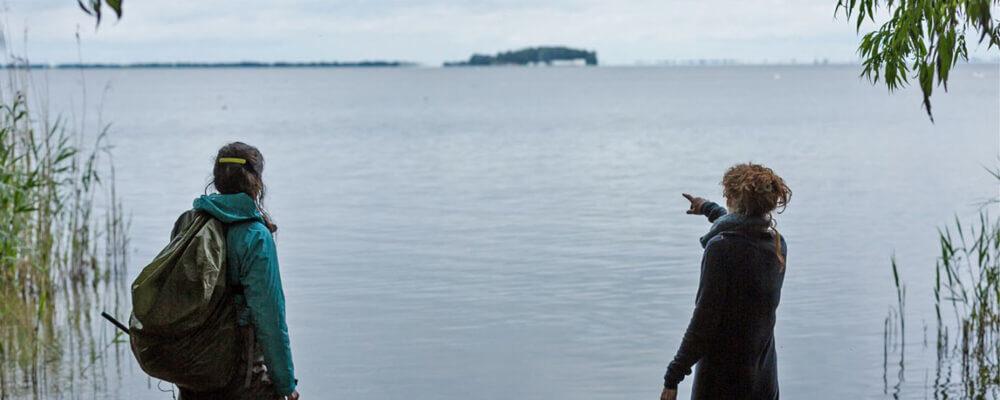 Vrouw wijst naar overkant water
